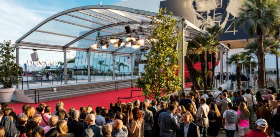 Cannes, France - May 24, 2014: Great Auditorium of the exit door at Cannes in France, the famous red carpeted stairs and crowd of people waiting at the gate output.
